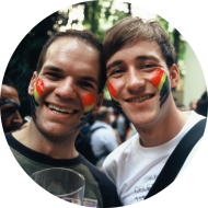 Two men smiling at a pride event