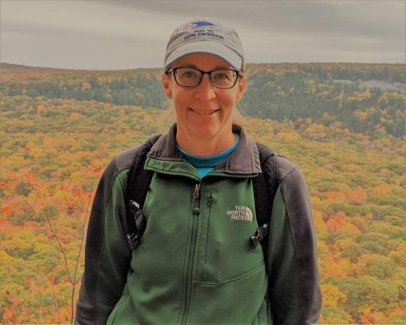 photo of Laura DeCicco with backdrop of treetops in autumn leaf colors
