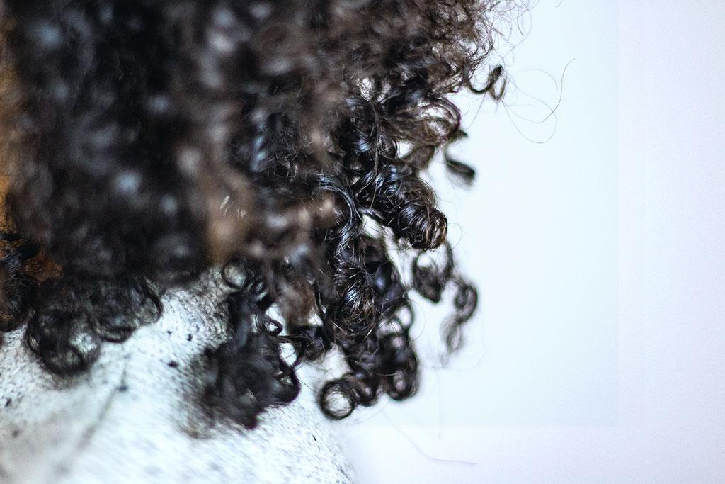 Eine Nahaufnahme auf die Afrolocken einer jungen Frau.