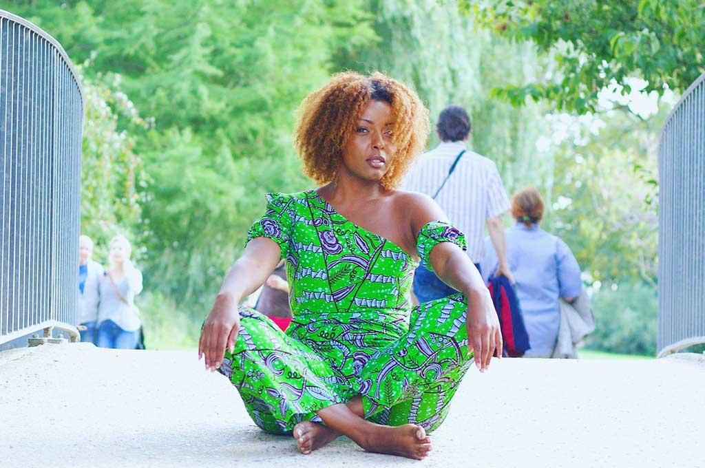 Die Ernährungswissenschaftlerin Magda sitzt auf einer Brücke und schaut in die Kamera.