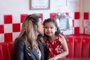 Mother kissing daughter in Busy Bee Cafe in Ventura, CA
