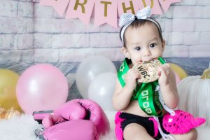 One Year Cake Smash Baby Boxer Girl Sitting Biting WBC Medal