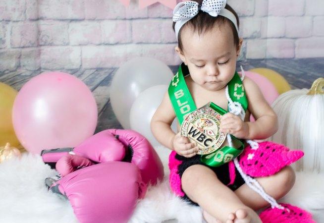 One Year Cake Smash Baby Boxer Girl Sitting Looking at WBC Medal