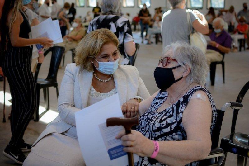 La ministra Martorano conversa con una señora que espera su primera dosis.