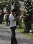 バラが咲き乱れるバラ園のなかで当サイト管理人の「花田昇崇」を遠景より撮影した写真。