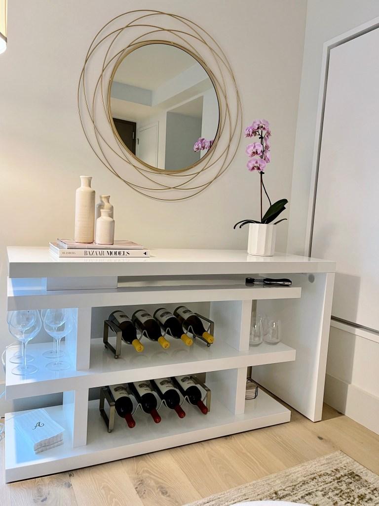 Living room book shelf wine rack home decor. gold mirror, coffee table books, modern aesthetic