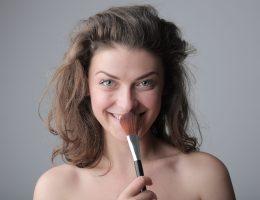 Femme qui tient une brosse à maquillage devant ses lèvres