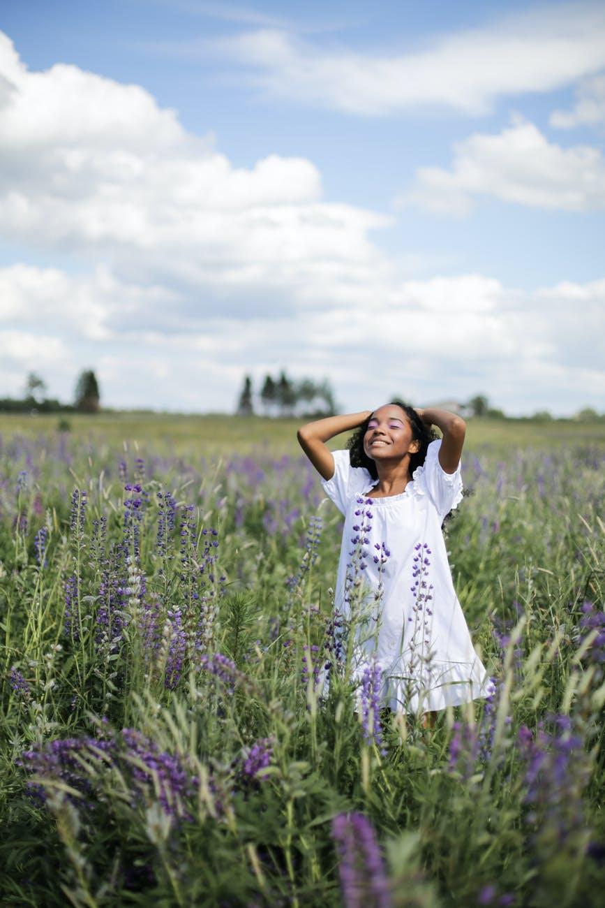 woman in white dress standing on purple flower field