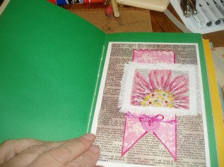 A hand printed flower on canver then hand stiched on a heavy water color paper..
