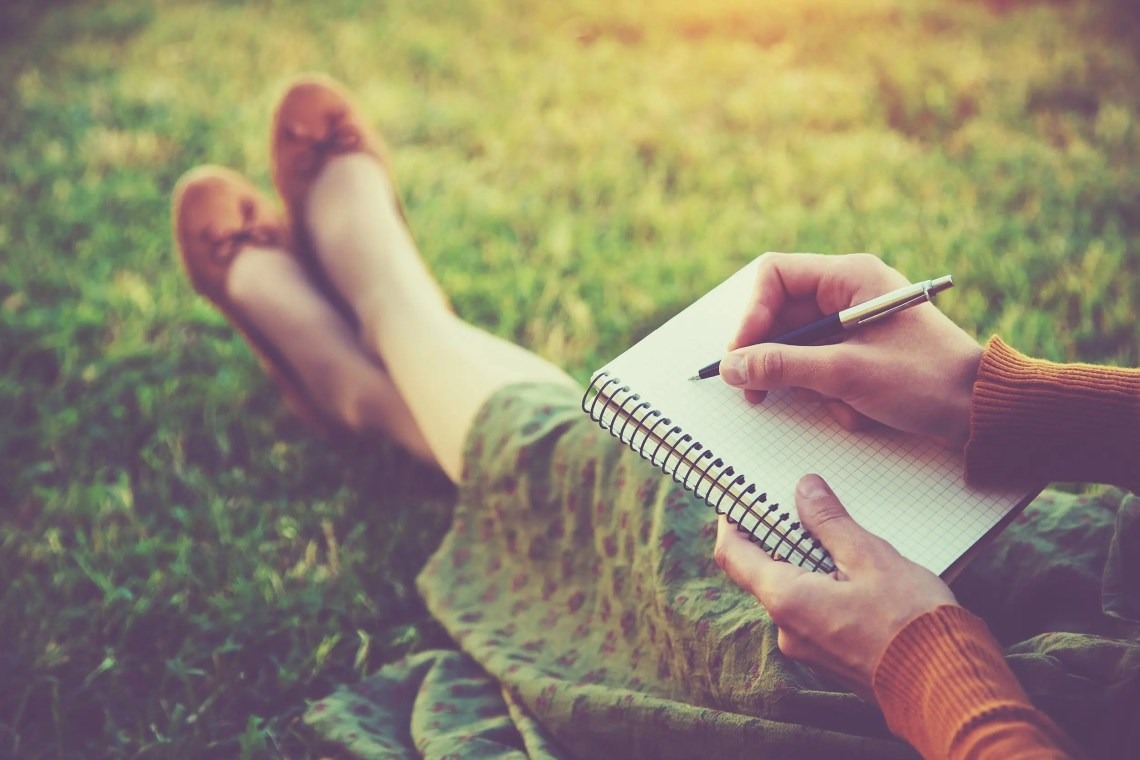 female hands with pen writing on notebook on grass outside choosing a new word for the year
