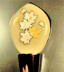 Wine or bottle stopper with gold and silver foil accents.