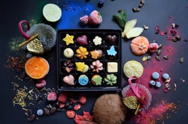 a box of 16 different chocolates in a variety of colours (brown, blue, pink, yellow, orange) and shapes (heart, star, flower, tea cup, round, square). Surrounding the box are raw ingredients including fruit, coconut, saffron and spices.