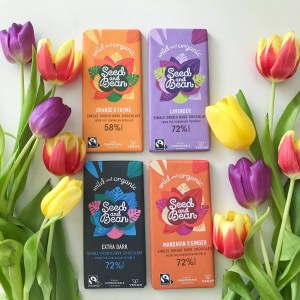 four different flavoured bars of seed and bean chocolate with colourful tulips arranged around them
