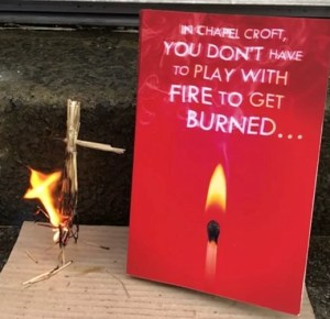 a copy of the burning girls book with a straw doll next to it which has been set alight