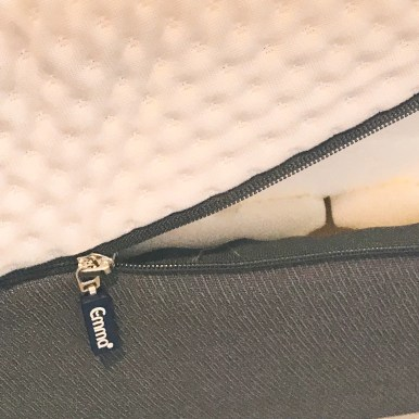 a close up photo of a partially unzipped cover on the mattress