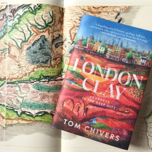 a copy of London Clay by Tom Chivers lying on top of a geological map of south east England