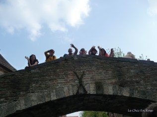 Passers by waving on the bridge