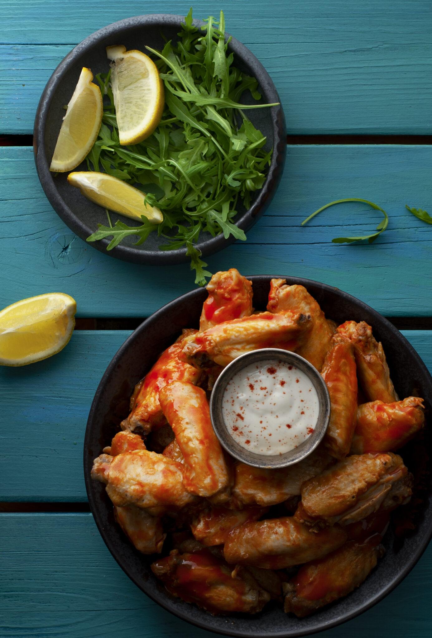 foto van chcickenwings en een salade op azuurblauwe tafel