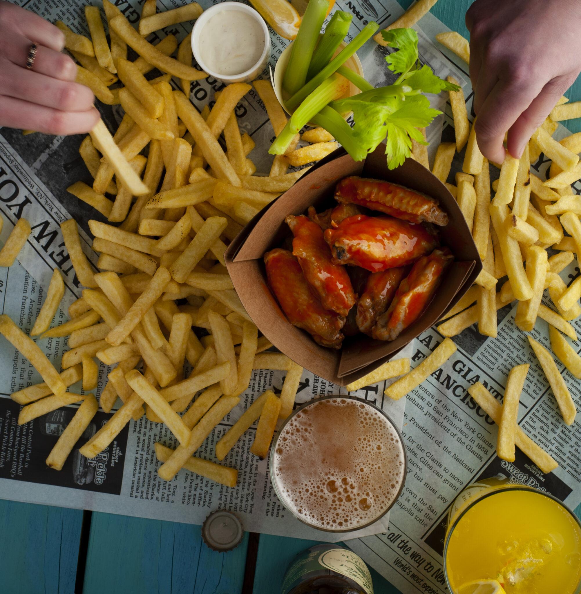 Foodfoto van chickenwings met frietjes en twee handen die frietjes pakken