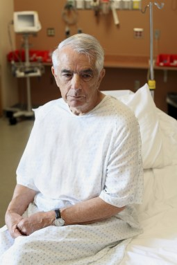 Unhappy elderly man sitting on hospital bed