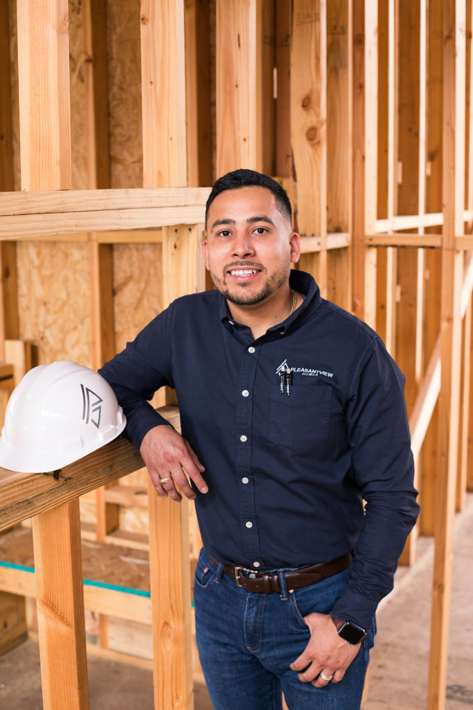 Contractor surrounded by wood frame of home while smiling