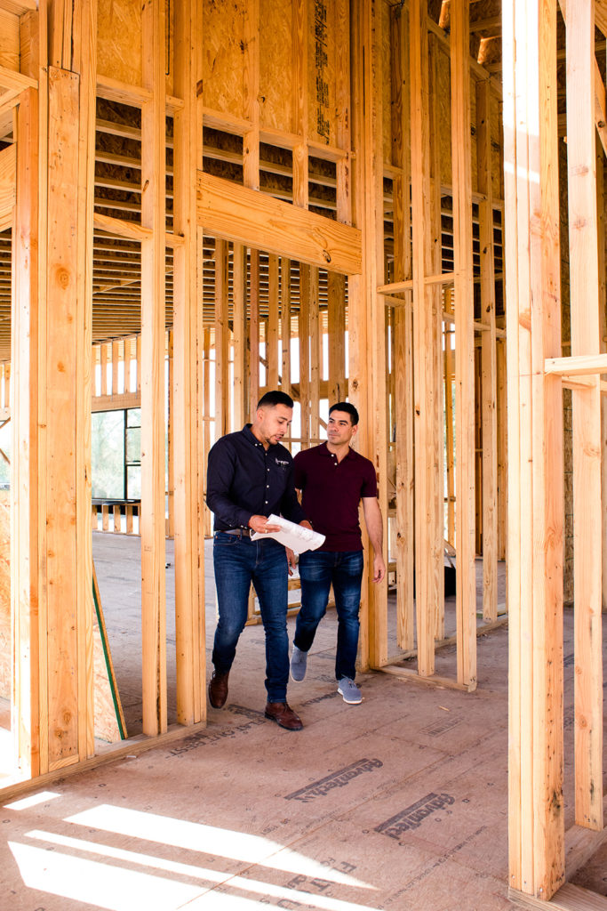 contractor working with client showing him the stages of home compared to the blueprint