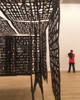 Pavilion Suspended in a Room 2005 made from steel by Cristina Iglesias with someone else looking at the information on it