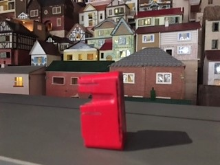 My red figure and its shadow facing the left way side angle in front of Village