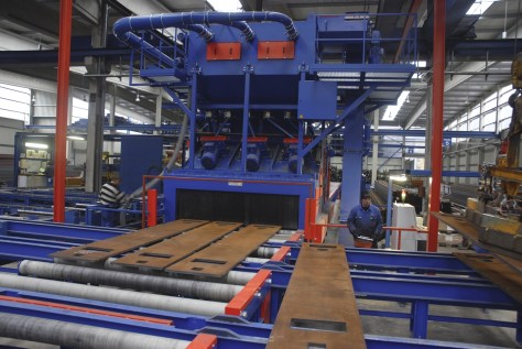 Steel plates and beams are transported through this Rosler RRB shot blast machine via roller conveyors.