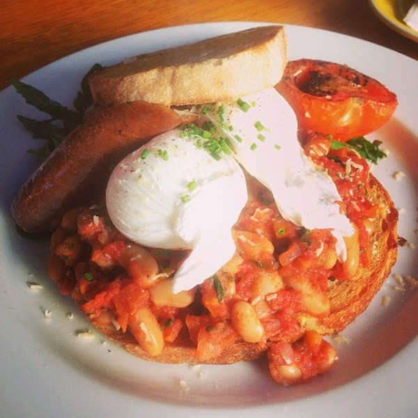 homemade baked beans with braised beef sausage and toasted organic sourdough topped with two poached eggs