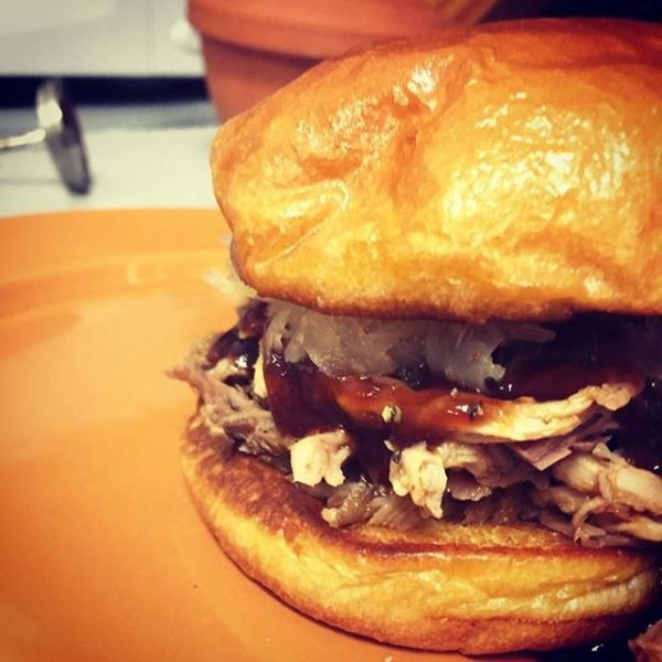 Pulled pork with smokey barbecue sauce and sauerkraut on a toasted brioche bun