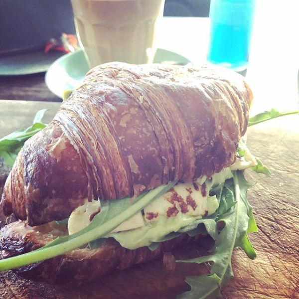 Warm croissant with grilled halloumi, a poached egg, avocado salsa & wild rocket, blue spirulina, pineapple, apple & lime juice and a triple shot latte