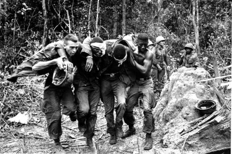"""Wounded U.S. paratroopers are helped by fellow soldiers to a medical evacuation helicopter on Oct. 5, 1965 during the Vietnam War. Paratroopers of the 173rd Airborne Brigade's First Battalion suffered many casualties in the clash with Viet Cong guerrillas in the jungle of South Vietnam's """"D"""" Zone, 25 miles Northeast of Saigon. (AP Photo)"""