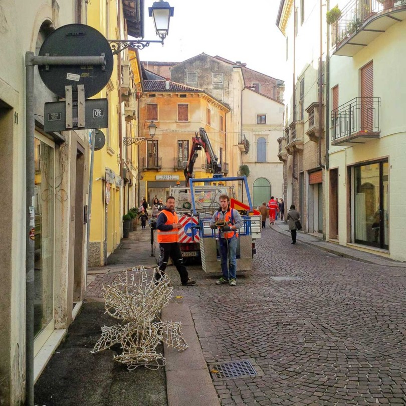 Workers hanging Christmas decorations in the historic centre - Vicenza, Italy - rossiwrites.com