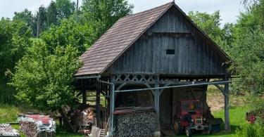 Kozolec - Wooden hayrack barn with a red tractor, Bela Krajina, Slovenia - www.rossiwrites.com