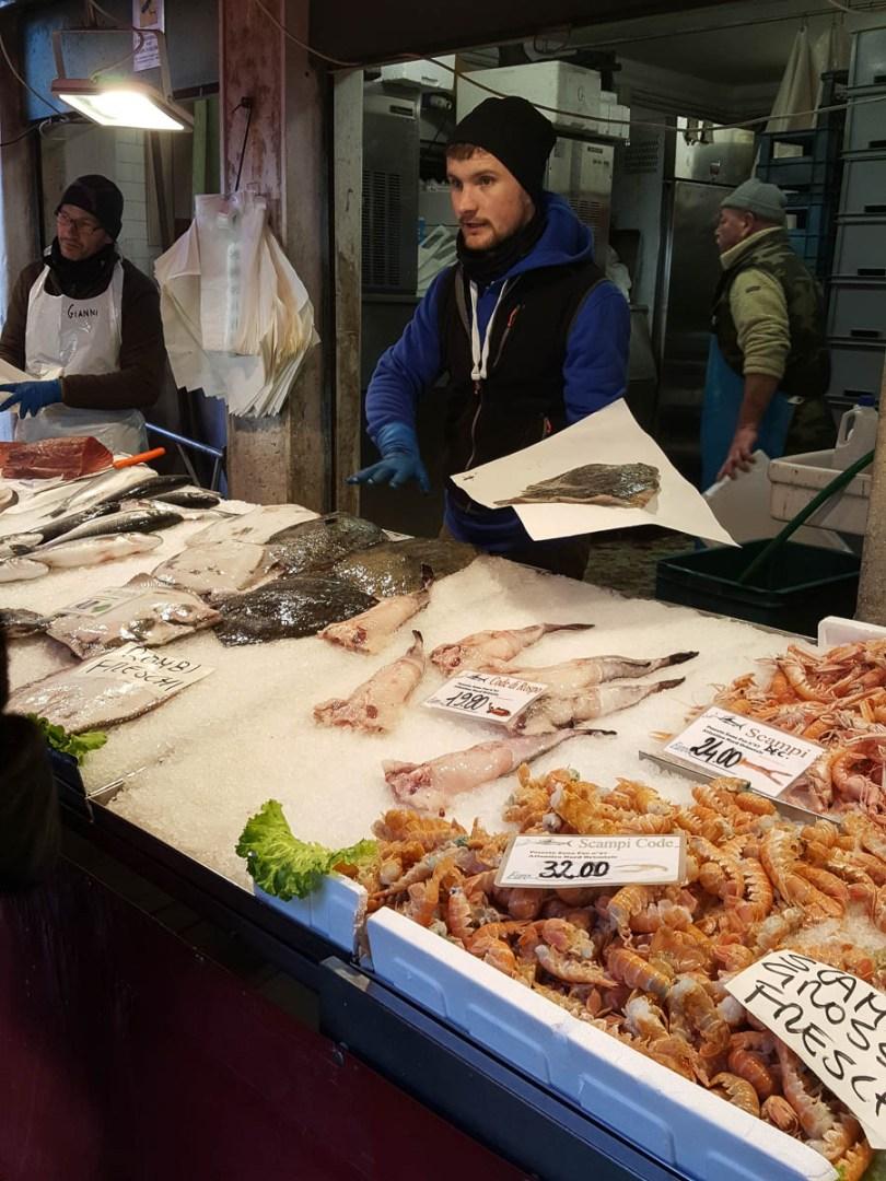A fishmonger selling fish - Rialto Fish Market, Venice, Italy - www.rossiwrites.com