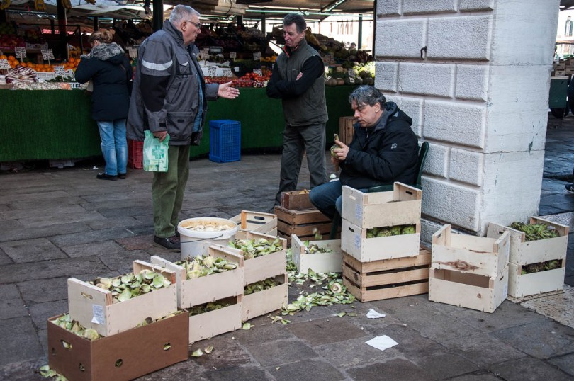 An artichoke trimmer with two friends - Rialto Market, Venice, Italy - www.rossiwrites.com