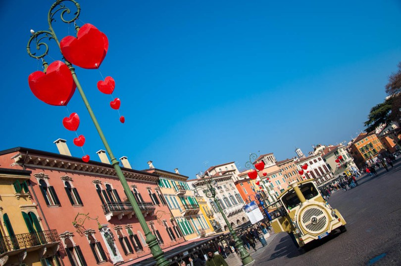 Piazza Bra decorated with hearts and a tourist sightseeing train - Verona, Italy - www.rossiwrites.com
