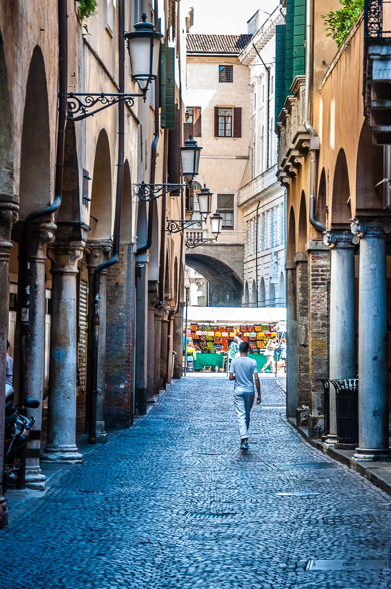 A boy in white walking down a cobbled street towards the daily market on Piazza delle Erbe - Padua, Italy - rossiwrites.com