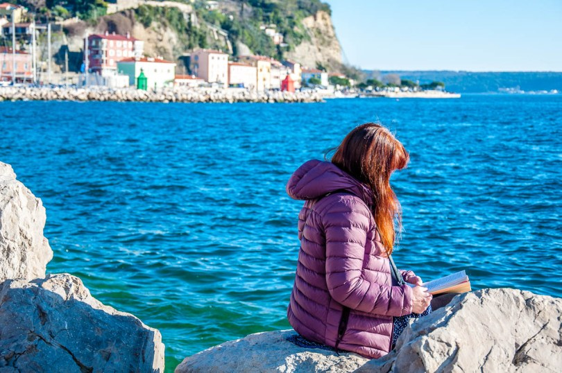 Reading a book on the seafront - Piran, Slovenia - www.rossiwrites.com