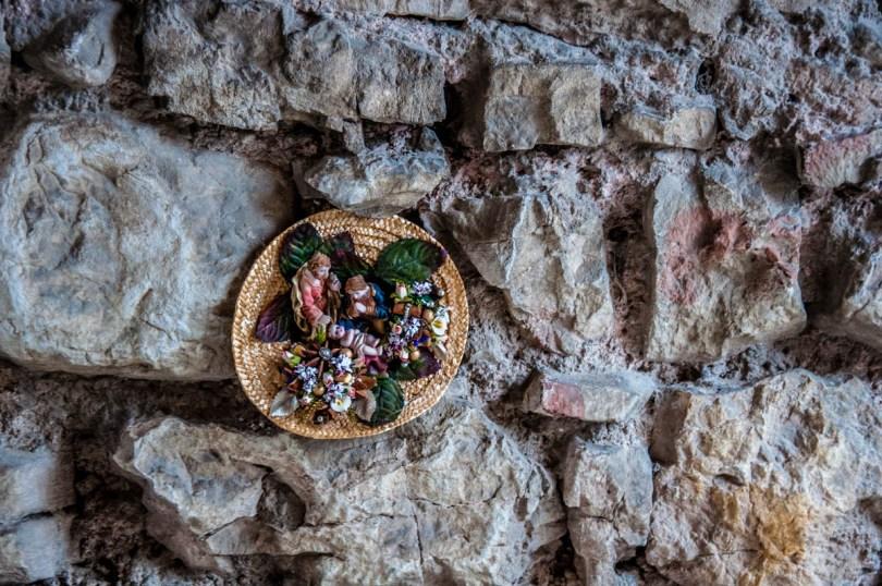 Nativity scene in a straw hat tucked inside a stone wall - Campo di Brenzone, Lake Garda, Italy - www.rossiwrites.com