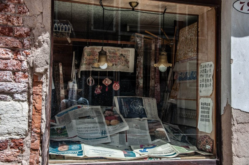 Shop window covered with newspapers - Venice, Italy - rossiwrites.com