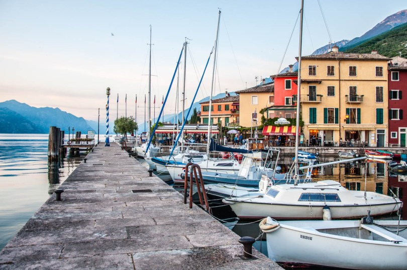 Colourful houses and boats in the small harbour next to Lake Garda - Castelletto sul Garda, Veneto, Italy - rossiwrites.com