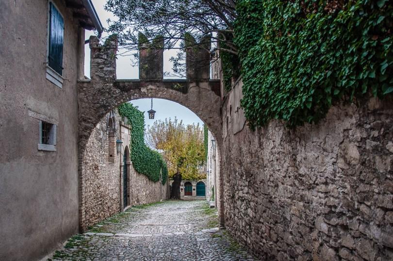 A cobbled street with the thick defensive wall of Villa Guarienti di Brenzone - Punta di San Vigilio - Lake Garda, Italy - rossiwrites.com