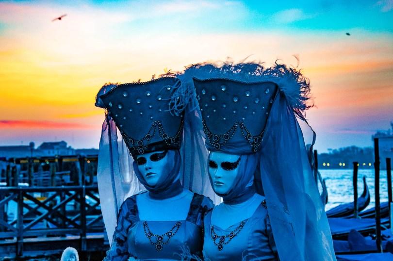 Two beautiful Venetian masks under an orange dawn - Venice, Italy - rossiwrites.com