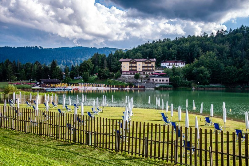 View of Lake Lavarone with a grassy beach with sun loungers - Trentino, Italy - rossiwrites.com