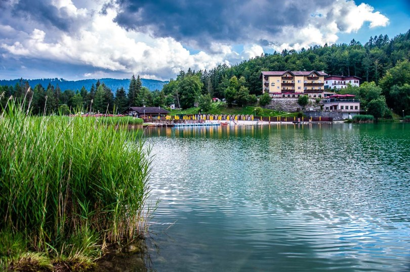 View of Lake Lavarone with a hotel and sandy beach in the distance - Trentino, Italy - rossiwrites.com