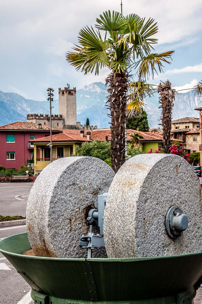 Olive grinding stones with the Scaliger Castle in the backdrop - Malcesine, Italy - rossiwrites.com