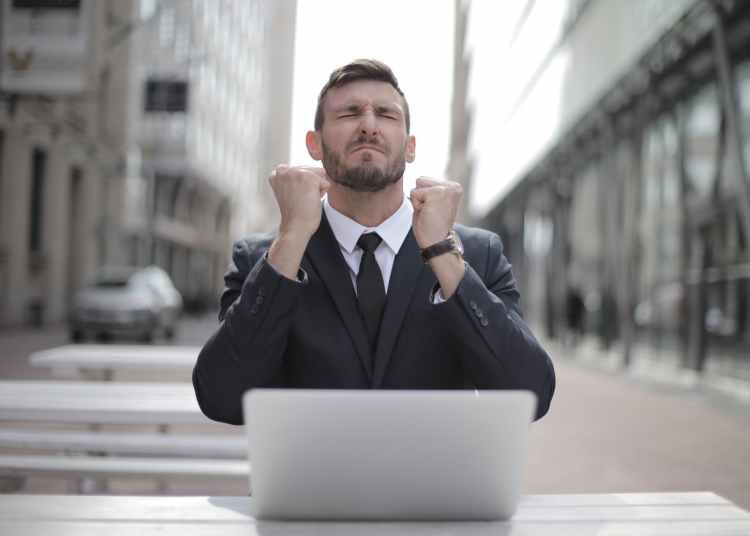 man in black suit sitting on chair beside buildings