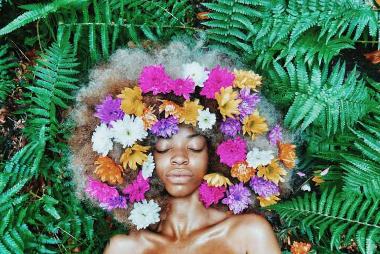 woman with floral headdress lying on green leaf plants